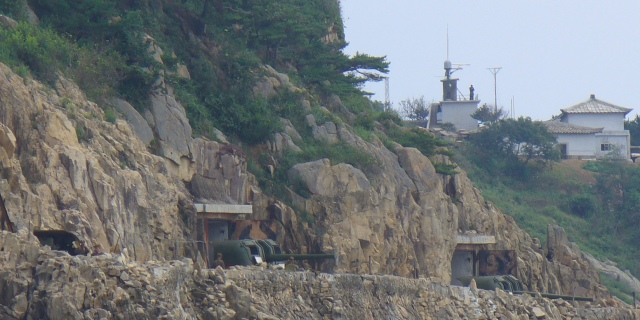 Turrets positioned on a cliff face the Yellow Sea, also known as the Sea of Japan