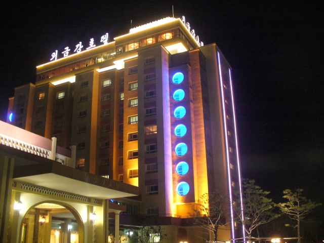 The Guemgangsan Hotel lit up at night, across from a village with no power