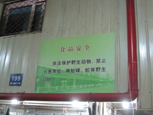 "A ""food safety"" sign which reads: ""In accordance with the law, please protect wildlife animals. The sale of frogs, toads snakes and other wildlife are prohibited."""