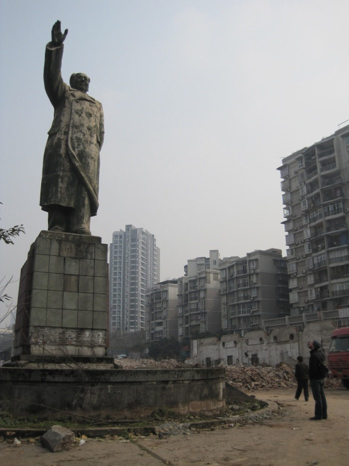 Shangqiao, Chongqing: A statue of Mao, the only thing left in a recently cleared plain of rubble, overlooks new construction projects