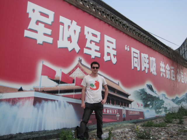 Me in front of propaganda pastered across a wall outside of Xitang, a watertown in Zhejiang Province, China