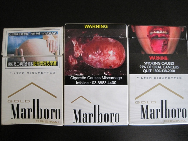 Cigarette boxes from Taiwan (far left), Malaysia (center), and Singapore (far right)