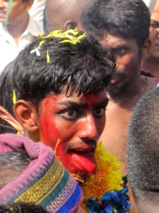 Covered in red powder, a devotee marches with his tongue and eyes flicking about