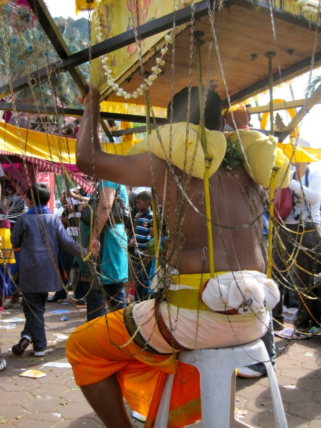 Man taking a break from carrying his kavadi