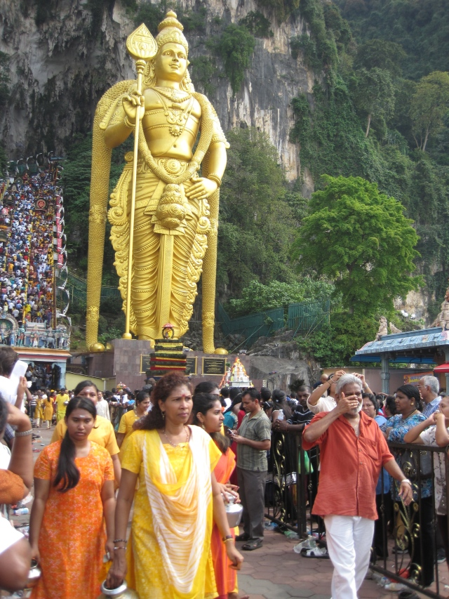 The statue of Lord Murugan watches over those coming and going from the caves