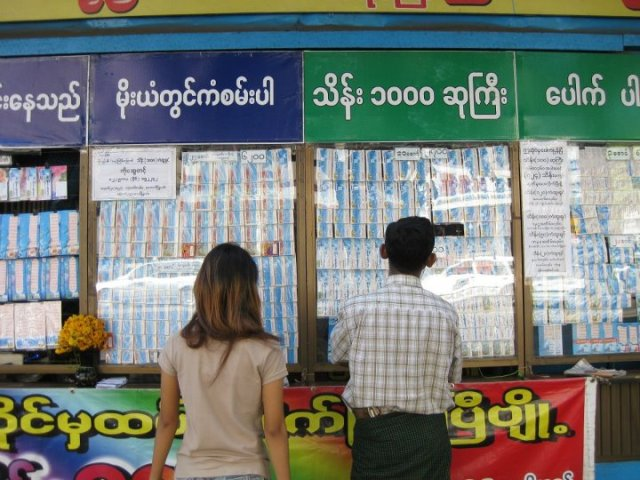 Two Burmese check out lottery numbers in Yangon