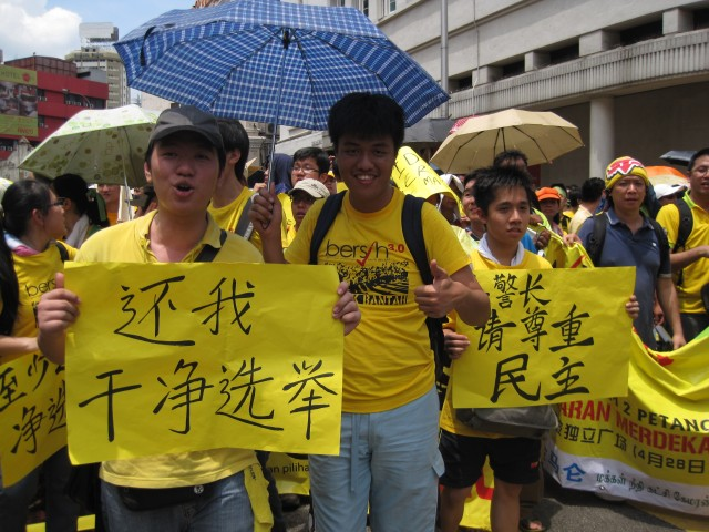Ethnic Chinese hold up signs reading 'Give us a clean choice' and 'Police chief, please respect democracy'