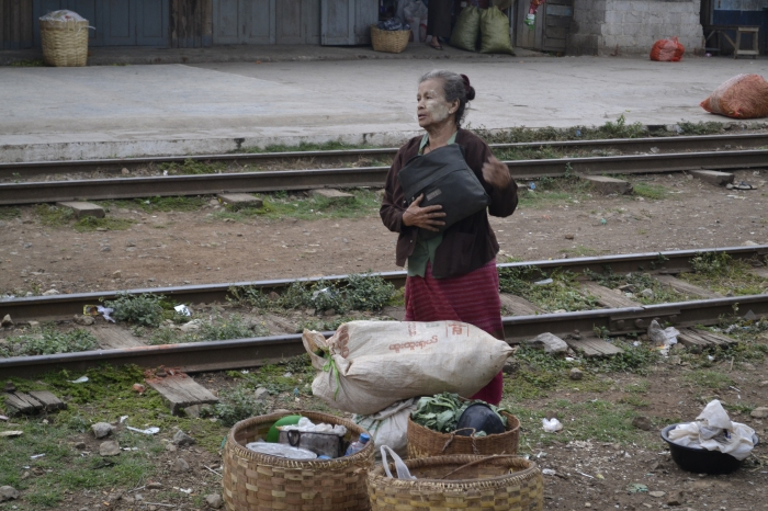 An old woman, waits, watches on the train tracks