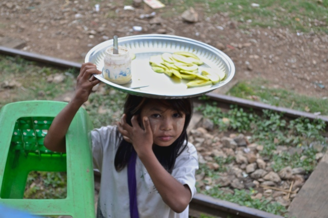 A girl sells slices of melon to passengers on the train