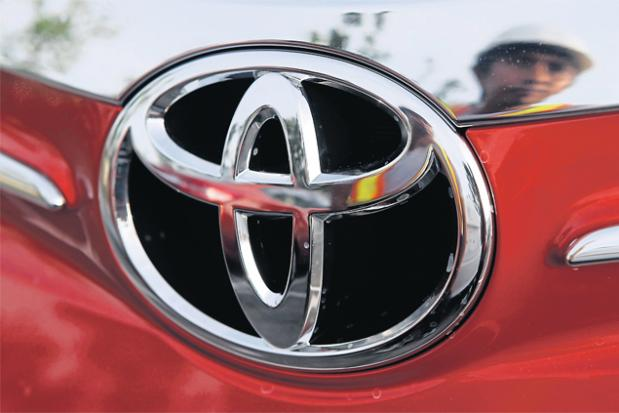 A worker is reflected next to the emblem of a Toyota Vios at the Toyota Philippines manufacturing plant in Sta Rosa in Laguna, south of Manila. (Reuters photo)