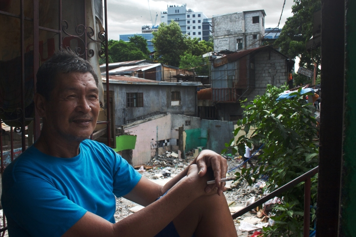 An old man on Kalayaan Avenue smokes a cigarette, with buildings from Bonifacio Global City in the background.
